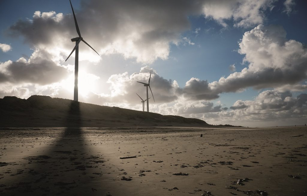 Wind turbines and cloudscape on a beach